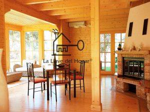 comedor salón diáfano de interior de casa de madera con vigas vistas y suelo de tarima