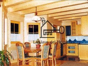 comedor y cocina en vivienda de madera con vigas vistas