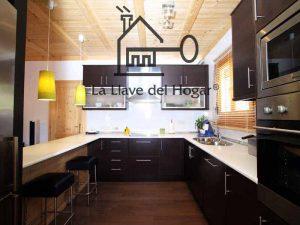 cocina con muebles marrones y barra americana