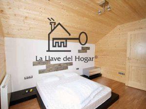dormitorio de matrimonio en casa de madera con pared del cabezal en obra