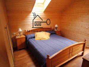 habitación de matrimonio en interior de casa de madera con ventana en techo tipo velux y paredes de tablilla