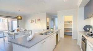cocina moderna con muebles blancos e isla que incorpora fregadero