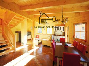 salón-comedor con vigas vistas y escalera abierta de madera