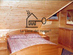 dormitorio de matrimonio con mansarda, paredes acabadas en madera