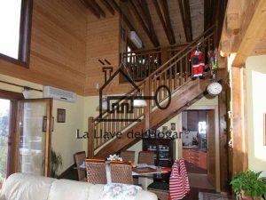 escalera de madera que sube a una galería donde se aprecia la estructura de cubierta completamente vista