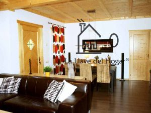 interior de una vivienda de madera con paredes acabado obra y parquet sintético en suelo. Techo de madera