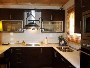 cocina moderna con muebles marrones y vitrinas superiores