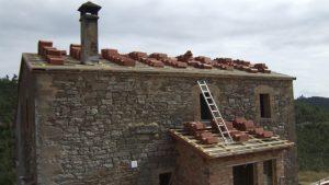 reforma de masía colocando nuevas tejas a la cubierta